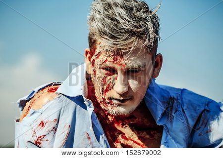Halloween zombie man handsome young vampire or bloody war soldier with wounds and red blood outdoors on blue sky