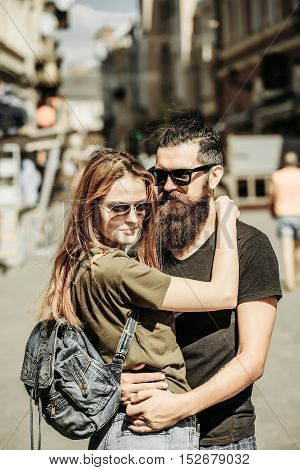 happy couple of handsome bearded man and pretty sexy cute woman or girl embracing in street in city center on summer sunny day with bag