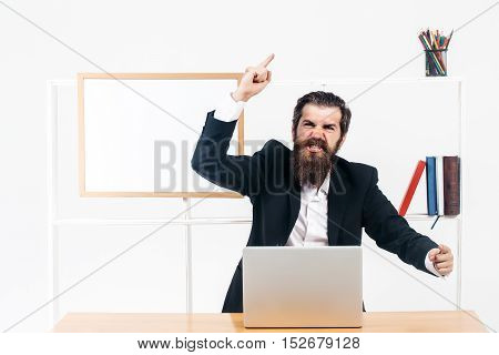 Bearded man in black suit speaks emotionally gesticulating by hands at desk with laptop in office