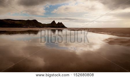 Three Cliffs Bay reflection on the shallow waters of a low tide on the Gower peninsula