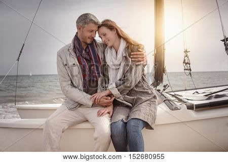 embracing couple on the boat with sea in background