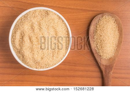 Demerara Sugar into a bowl over a wooden table