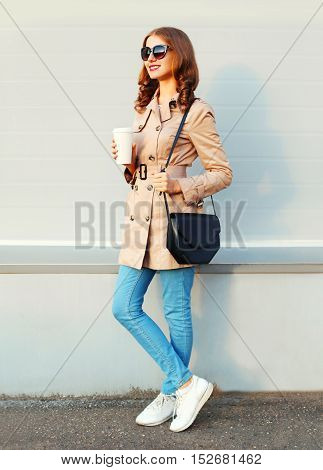 Fashion Pretty Young Woman With Coffee Cup Wearing A Coat And Handbag Clutch Over Grey Background