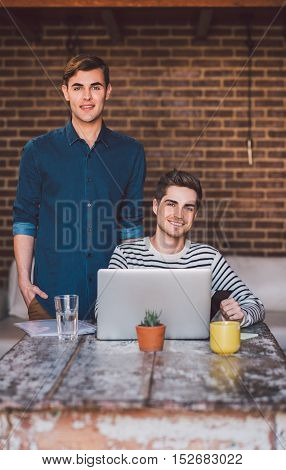 Portrait of a smiling young gay couple using a laptop together at a table at home