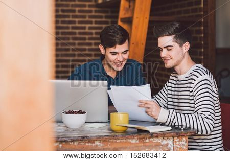 Young gay couple sitting at a table at home discussing paperwork over a laptop while working together on their home based business