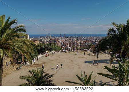 Barcelona, Spain - 24 September 2016:Park Guell Nature Square Placa de la Natura. Visitors on the terrace of Hypostyle Room Monumental  Zone at Park Guell. Barcelona City visible in the background.