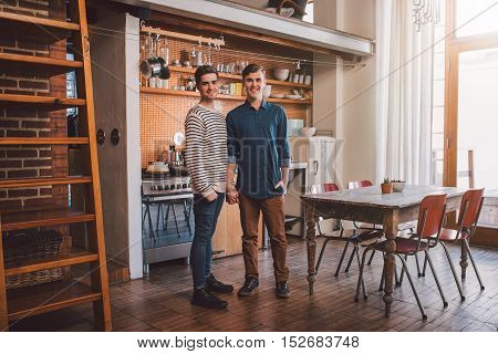 Portrait of an affectionate young gay couple standing side by side together in their loft apartment