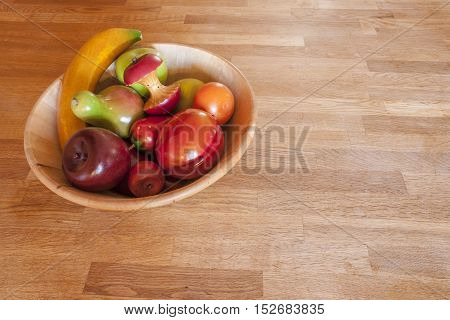 A bowl of wood-carved fruit looking almost good enough to eat on a butcher block counter
