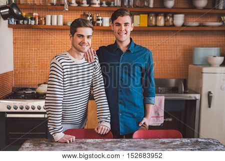 Portrait of an affectionate young gay couple standing side by side together in their kitchen