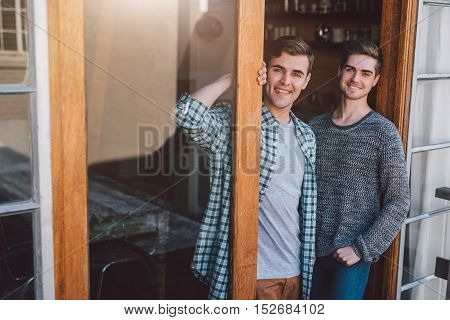 Portrait of a smiling young gay couple standing welcomingly at the door to their apartment