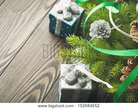 Fir tree branches with christmas gift shaped baubles, pine cones and green ribbons on dark wooden background. Copy space. Toned image