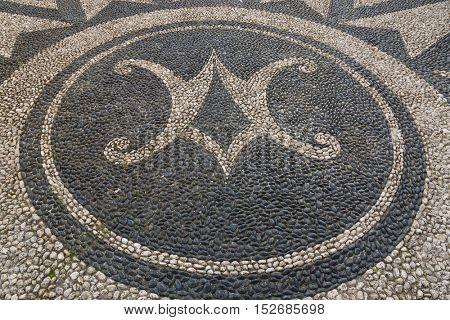 Beautiful large patterned pebble stone mosaic arranged in a symbol on pavement pedestrian street in Santa Margherita Ligure, Genova, Liguria, Italy