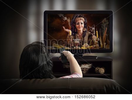 Woman sitting in brown couch watching occult TV channel. Mature female Egyptian witch posing with cat statuette smoking candles and mystique items on the screen