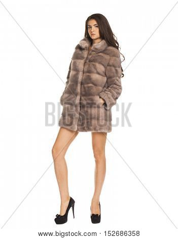 Portrait in full growth on a beautiful brunette woman short mink coat, isolated on white background
