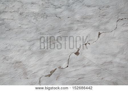White plastered wall divided by diagonal crack. Rough uneven texture