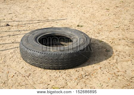 Old tire on the sand. Broken tire in sand
