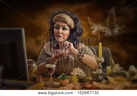 Female Egyptian astrologer working in internet. The mature black haired diviner sits at the desk opposite a monitor.  Fortuneteller holds dried bones in hands and attentively looks at the screen