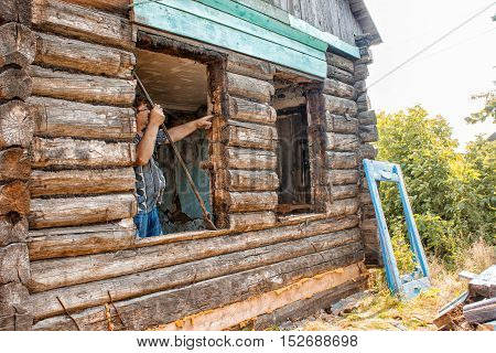man changes the window in a wooden house on summer day