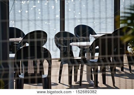 Chairs and tables by the sea in a beautiful summer day