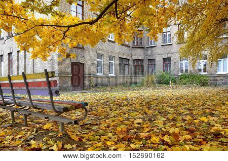 Autumn old courtyard with an old brick building and a bench under the yellow maple.