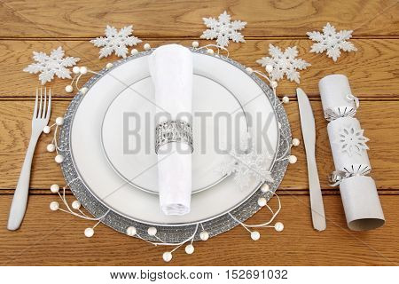 Christmas dinner table setting with white porcelain plates, cutlery, linen serviette with silver napkin ring, snowflake bauble decorations and cracker over oak background.