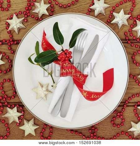 Christmas dinner table setting with white porcelain plate, cutlery, red ribbon, napkin, holly, mistletoe, star and bead bauble decorations over oak wood background.