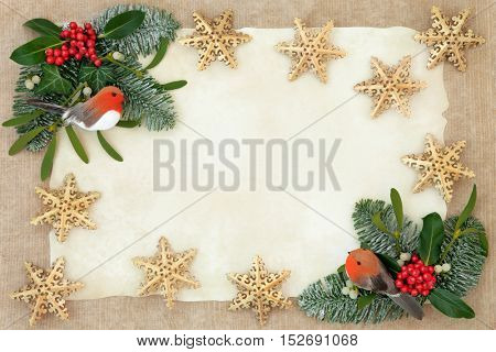 Christmas background  border with gold snowflake bauble and robin decorations, holly, ivy, mistletoe and snow covered winter greenery over old parchment and hemp paper.