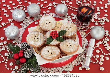 Mince pie christmas cakes, mulled wine drink, holly, winter greenery and silver cracker and bauble decorations over red background.