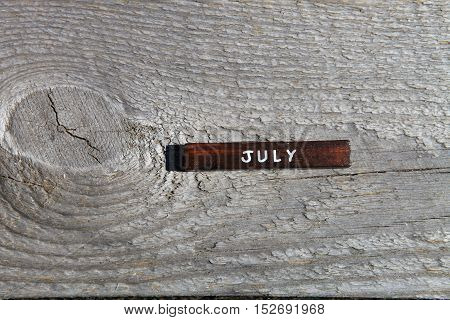 Wooden Cube With The Name Of The Month At The Old Board. July