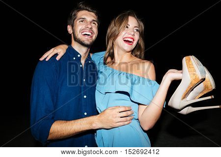 Cheerful young couple with shoes in hands hugging and having fun at night