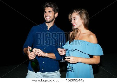 Happy young couple opening bottle of champagne on the beach at night