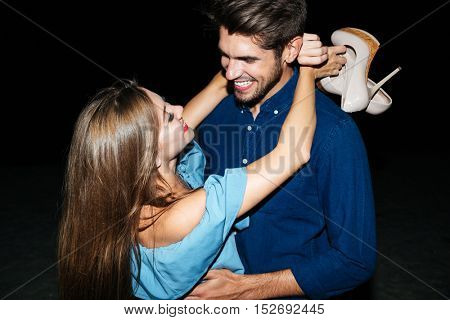 Cheerful young couple with shoes in hands standing and embracing at night
