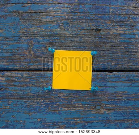 Yellow sticker and pins on old wooden wall