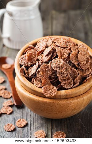 Chocolate cornflakes for breakfast in a bamboo plate on old wooden background. Selective focus.