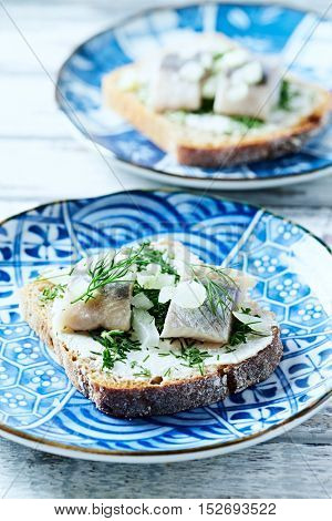 Sandwiches with cream cheese, salted herring and herbs