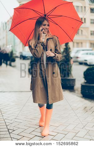 Feeling ptotected at this autumn day. Full length of attractive young smiling woman in colorful rubber boots carrying umbrella and talking on the mobile phone while walking by the street