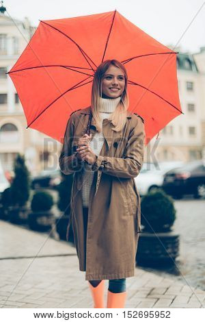 Woman under umbrella. Attractive young woman carrying umbrella and smiling while standing on the street