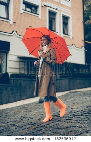 Walking around the city. Full length of attractive young smiling woman in rubber boots carrying umbrella and coffee cup while walking down the street