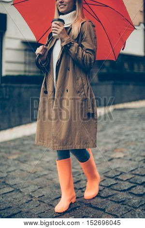 Enjoying autumn day. Cropped image of attractive young smiling woman in rubber boots carrying umbrella and coffee cup while walking down the street