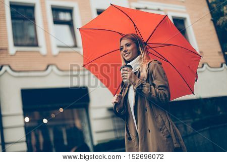 City life. Low angle view of attractive young smiling woman carrying umbrella and coffee cup while walking along the street