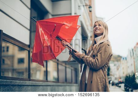 No more rain! Low angle view of attractive young woman carrying umbrella and looking up with smile while standing on the street