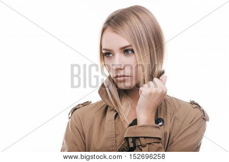 Autumn beauty. Attractive young woman in coat adjusting her collar and looking away while standing against white background