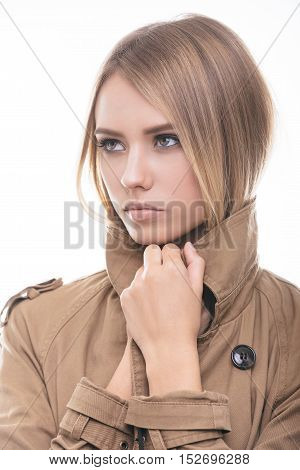 Feeling warm and trendy. Attractive young woman in coat covering her neck with collar and looking away while standing against white background