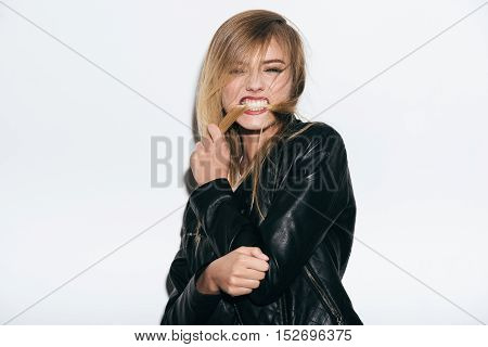 Funky beauty. Funky young woman in leather coat holding her hair in mouth while standing against white background