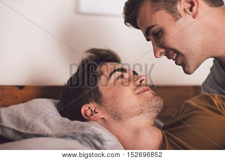 Affectionate young gay couple lying face to face together in bed in the morning