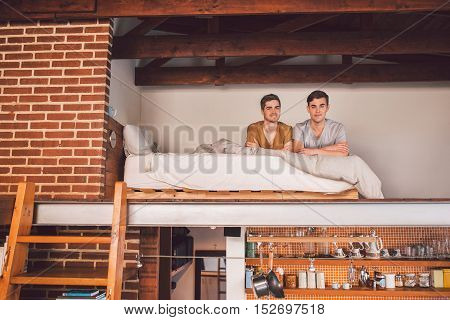 Portrait of an affectionate young gay couple lying together in their loft bedroom in the morning