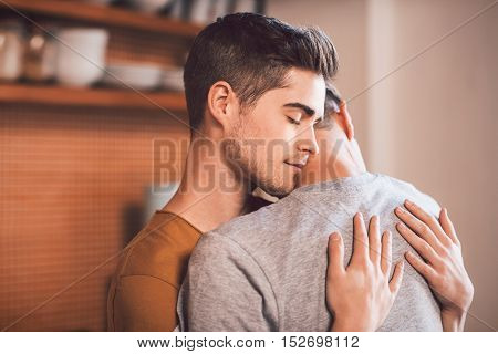 Affectionate young gay couple hugging each other with their eyes closed while standing in their kitchen in the morning