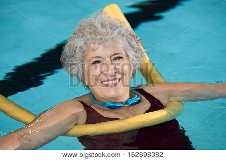 Senior woman doing aqua fitness with swim noodles. Mature woman doing water aerobics with a yellow noodle. Old woman in swimming pool doing aquarobic and rehabilitation exercise.