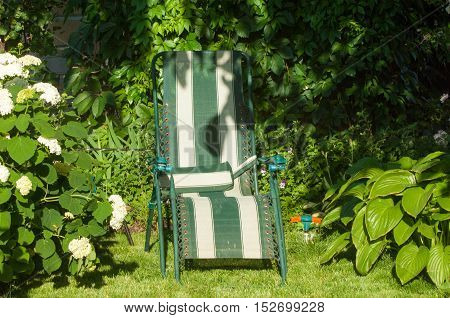 portable chair in the garden comfortable chair typically upholstered with side supports for a person's arms.