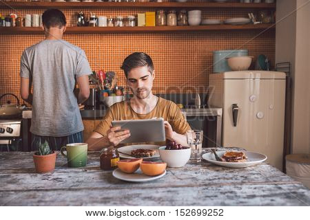 Content young gay couple using a digital tablet and preparing breakfast in their kitchen in the morning